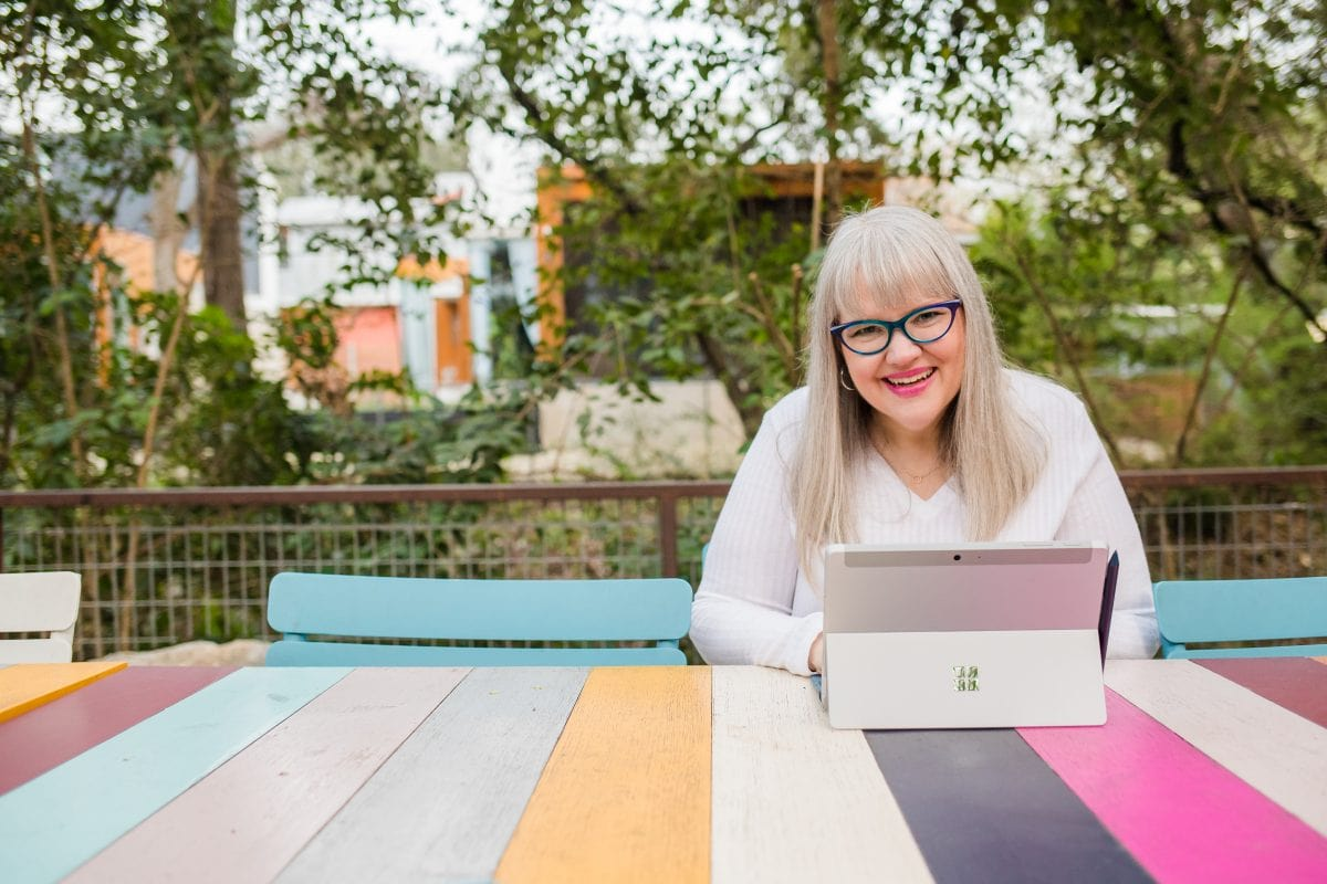 Christine Tremoulet seated at a colorful table with her laptop in front of her.